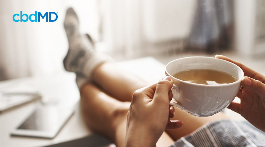 A woman sits with her feet     on a coffee table holding a white coffee cup
