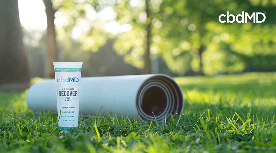 A grey yoga mat sits rolled     on the grass next to cbd recover 750 mg