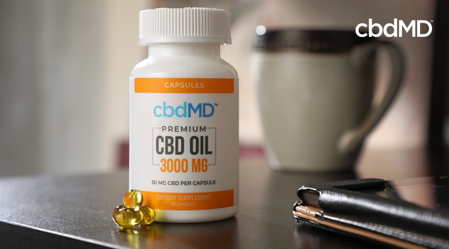 A bottle of 3000 mg cbd oil capsules sits on a night stand