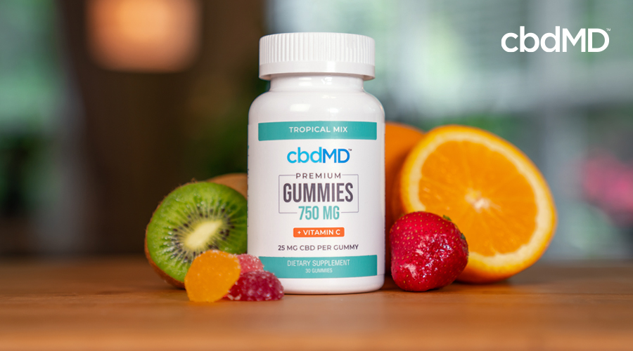 A bottle of 750 mg cbd gummies from cbdmd sits on a table near some fruit