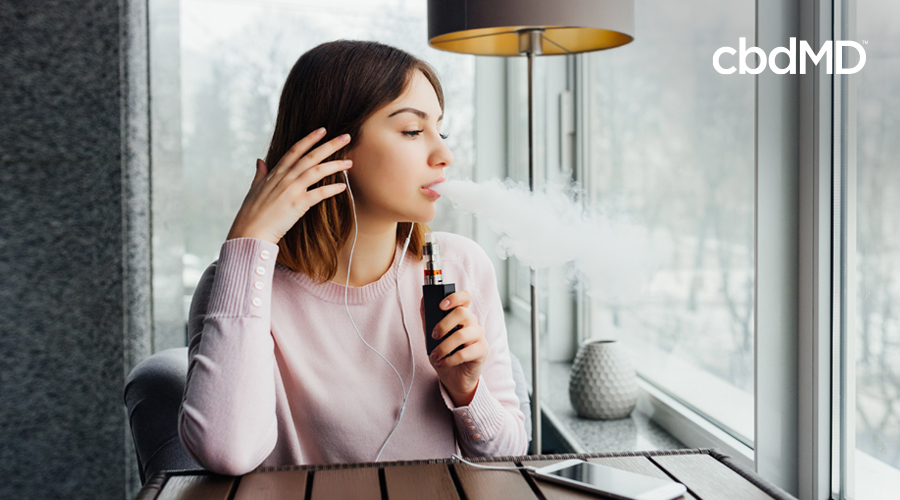 A dark haired woman sits in a coffee shop and blows out a cloud of vape smoke