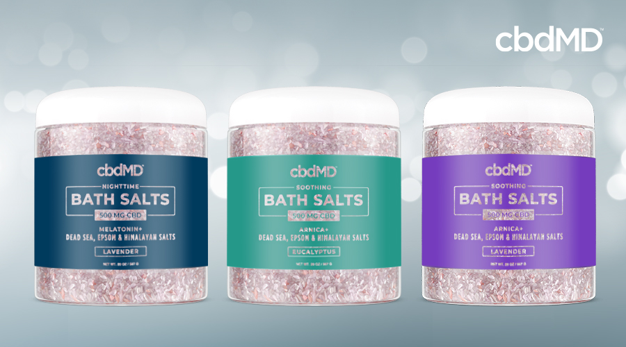 CBD bath salts from cbdmd in lavender, eucalyptus, and nighttime lavender sit in a row against a blue background