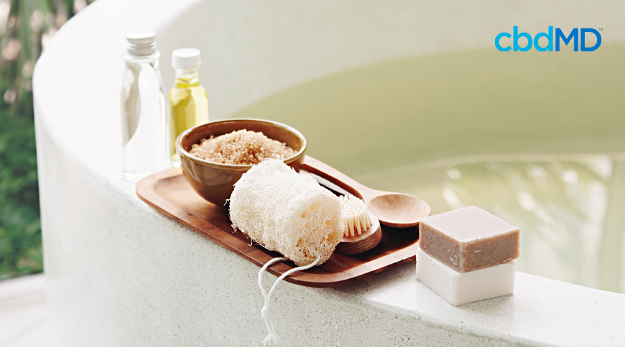 Essential oils, cbd bath salts, soap, and other bath supplies sit on the side of a tub