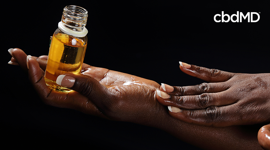 The arms of a dark skinned woman hold a bottle of argan oil as she applies it to her skin