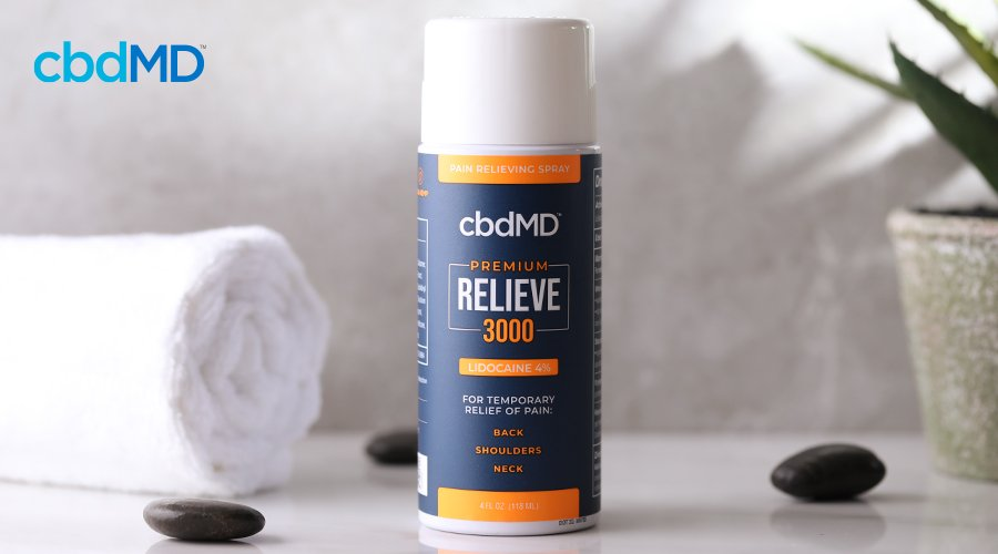 A bottle of relieve spray with lidocaine from cbdmd sits on a bathroom counter