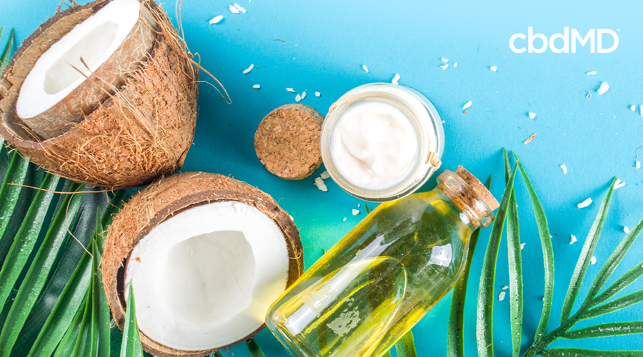 Two halves of a coconut lay among palm fronds near a jar of cream