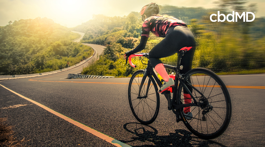 A woman dressed in black and pink riding gear rides her bike down a broad and twisting road