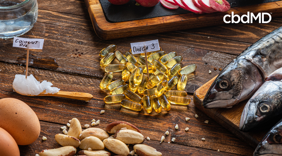 A pile of capsules marked omega 3 sits near a group of nuts, three fish, coconut oil, and eggs