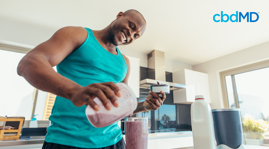 A man in a green tank top smiles as he makes himself an early morning protein shake