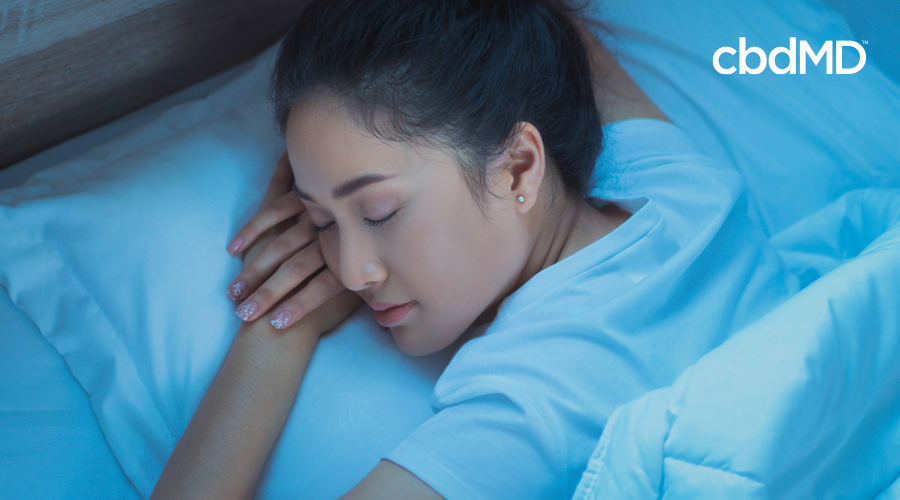 A woman with painted fingernails sleeps soundly in a blue shirt in her blue bed