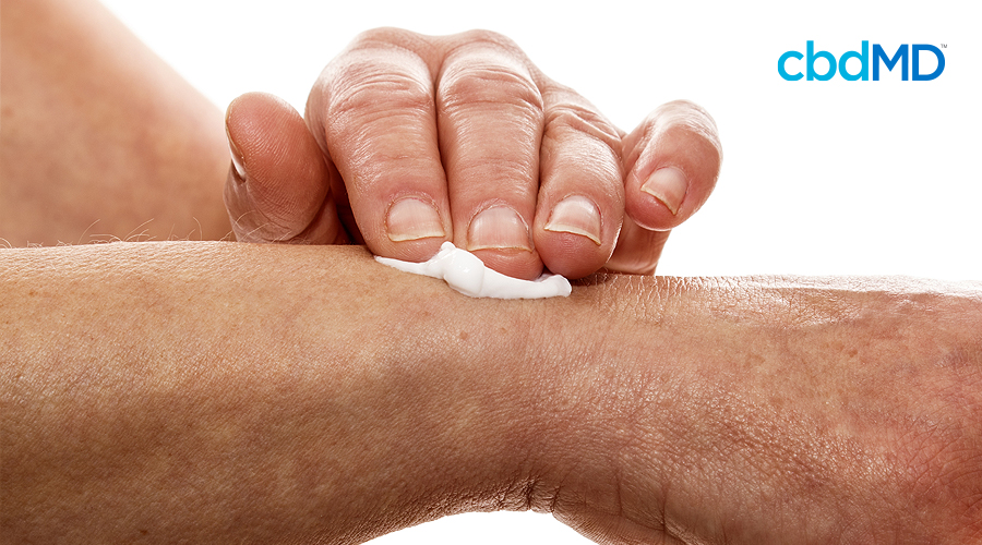 An arm rests up across the image with a hand rubbing white cbd cream at the wrist