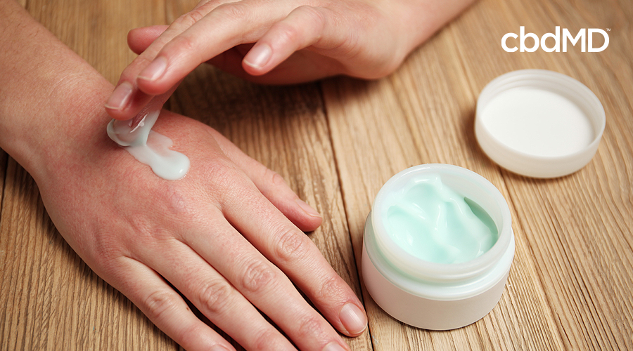 A feminine hand rubs light green cbd cream on the top as it rests on a wooden table