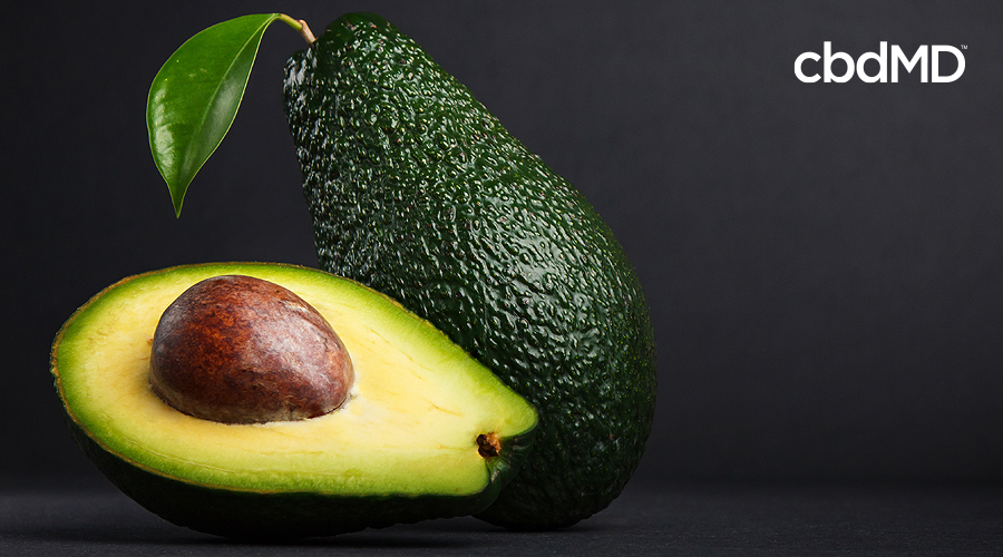A whole avocado and a halved avocado sit next to each other against a black background