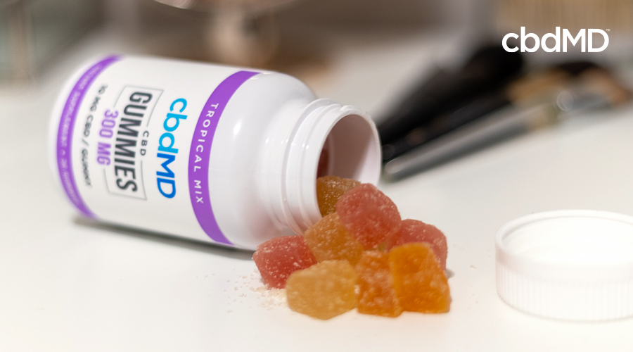 A bottle of cbd gummies from cbdmd sits on its side with gummy pieces spilling out