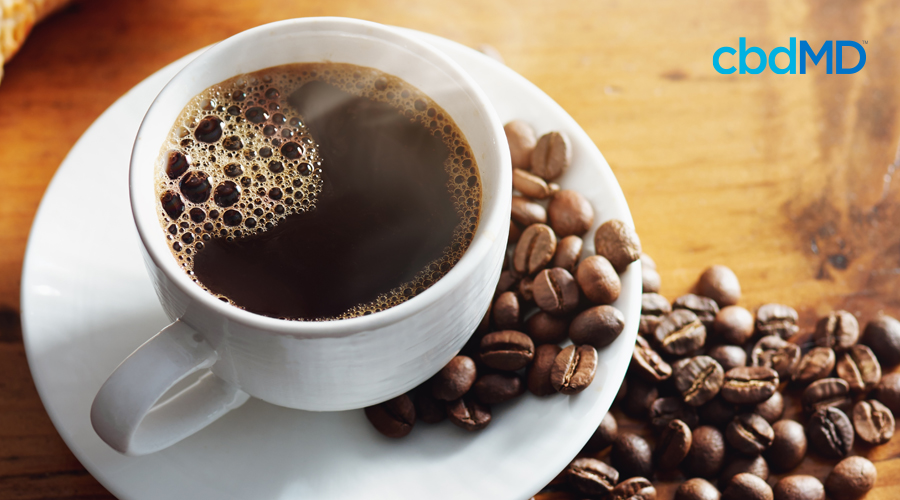 A fresh cup of coffee in a white mug sits on a saucer among roasted coffee beans