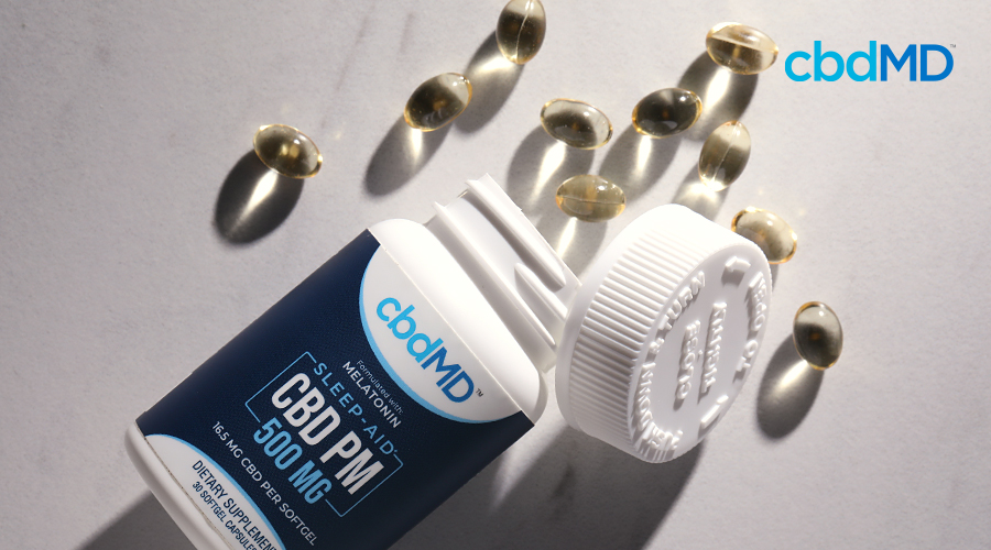 A bottle of cbd pm capsules lays on its side with capsules spilling out of the top