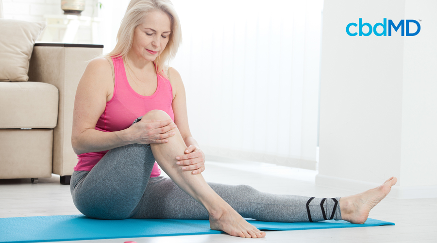 Older woman with light hair sits on aqua yoga mat in pink sleeveless shirt and gray workout pants while massaging knee