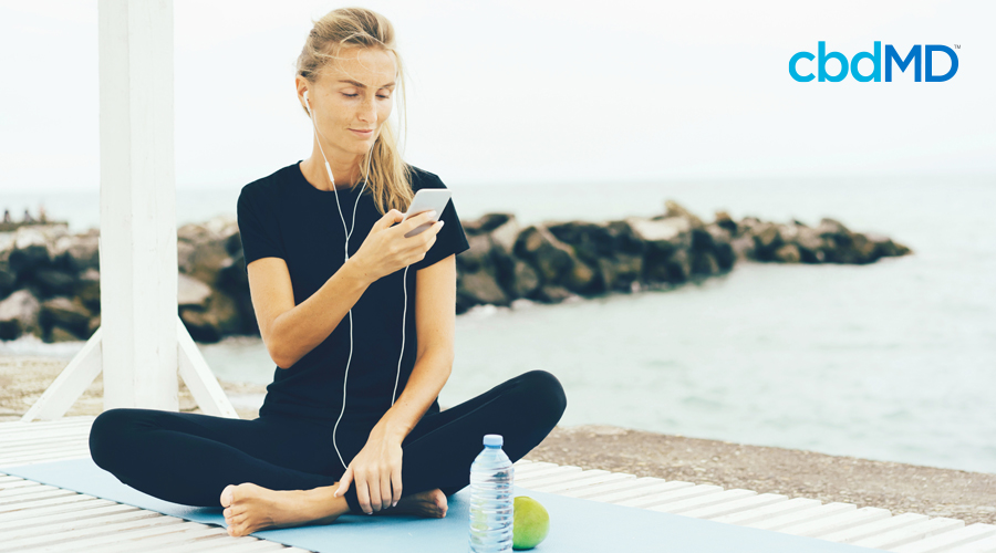 Fit woman with blonde hair sits criss-cross on light blue yoga mat at the beach looking at phone while wearing headphones and surrounded by water