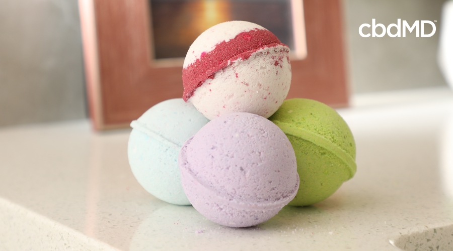 A small stack of four cbd bath bombs from cbdmd sit on a bathroom countertop in various colors