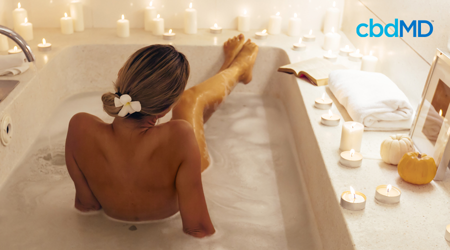 A woman with blond hair pulled up and tied with a ribbon sits in a bubble bath surrounded by lit candles