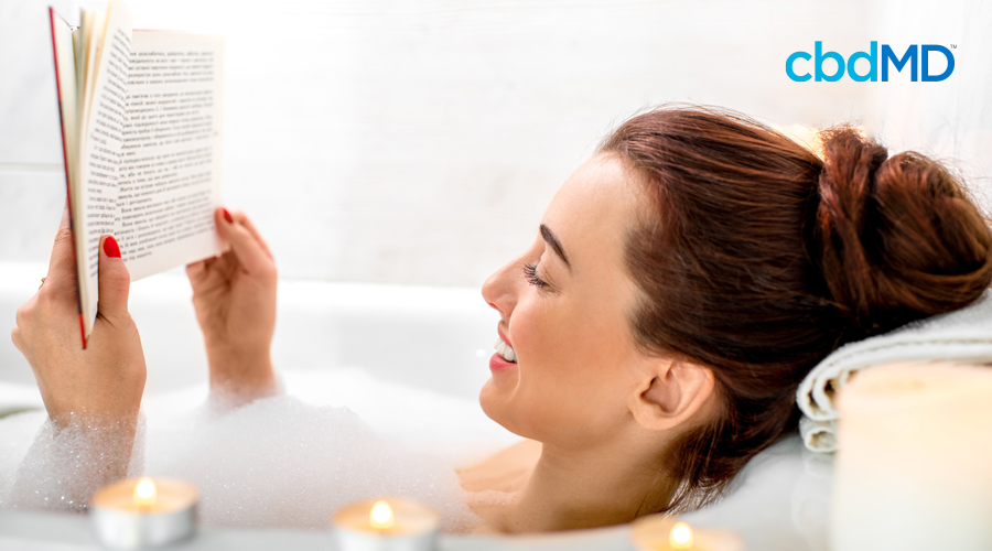 A dark haired woman sits up to her neck in a bubble bath holding up a book while she reads