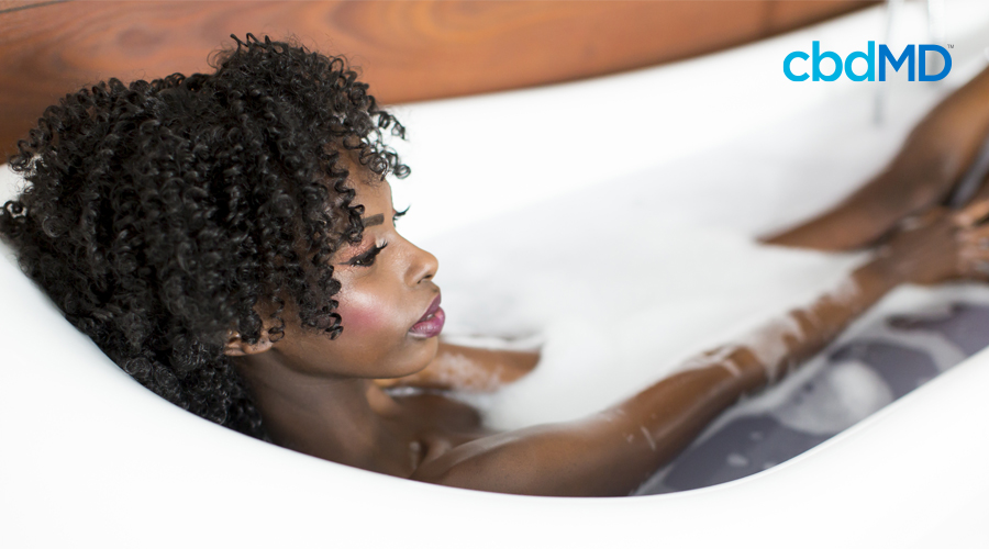 A dark skinned woman with curly dark hair sits in a curved bath tub filled with bubbles