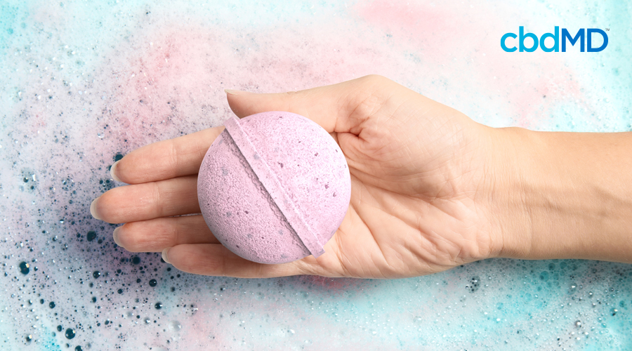 A woman's delicate hand holds a pick cbd bath bomb above a tub full of bubbly water