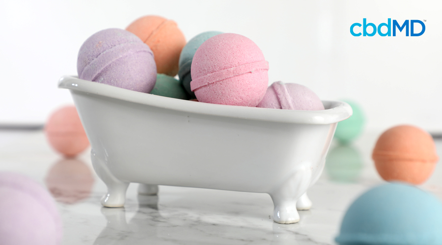 A miniature claw foot tub full of multi-colored cbd bath bombs sits on a bathroom counter