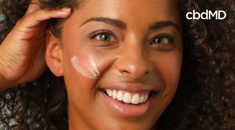 A dark skinned woman smiles as she puts lotion on her face