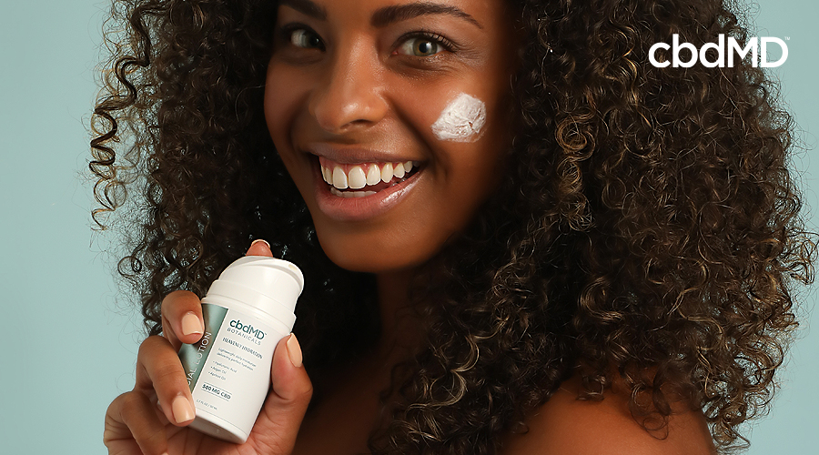 A dark skinned woman smiles with a streak of cbd botanicals cream on her cheek
