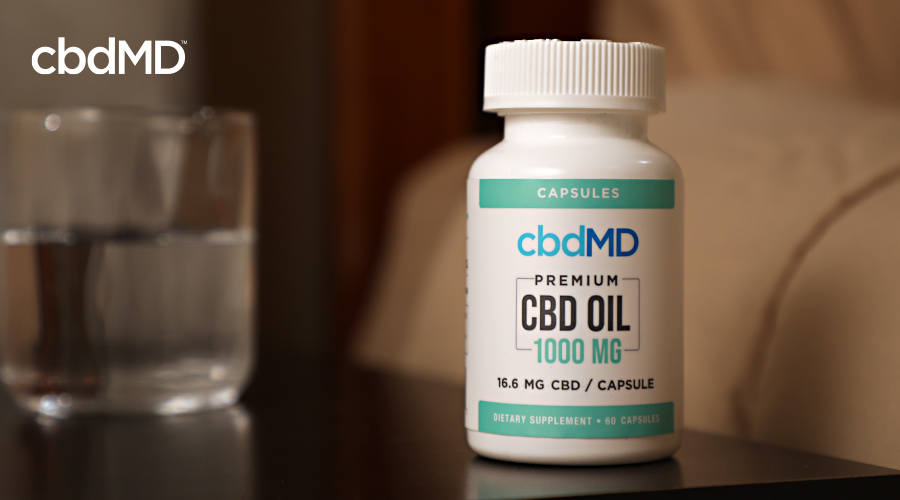 A bottle of 1000 mg cbd oil capsules from cbdmd sits on a nightstand