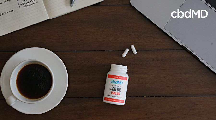 A bottle of 1500 mg cbd capsules from cbdmd lays on its side with a few pills spilling out