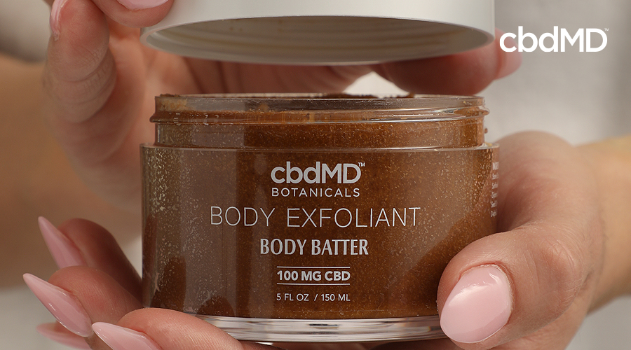 A jar of cbdmd body exfoliant body batter sits in a woman's hands
