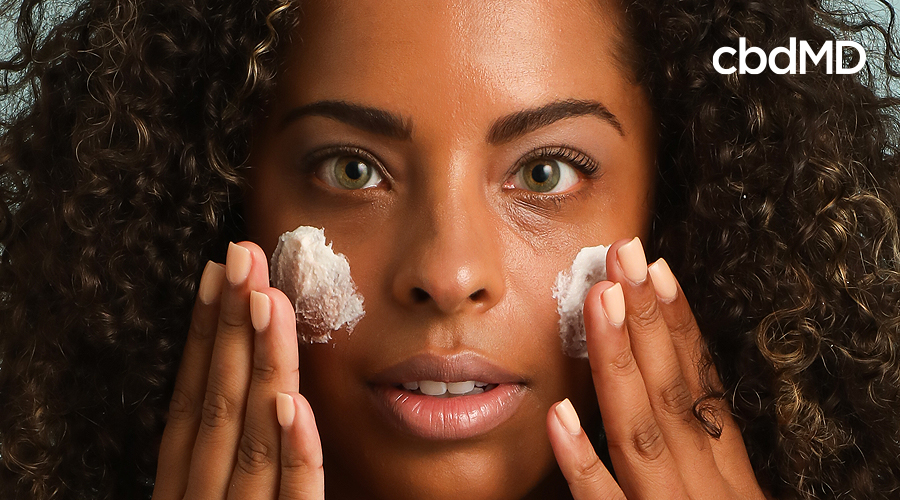 A dark skinned woman rubs cbd exfoliant from cbdmd onto her face
