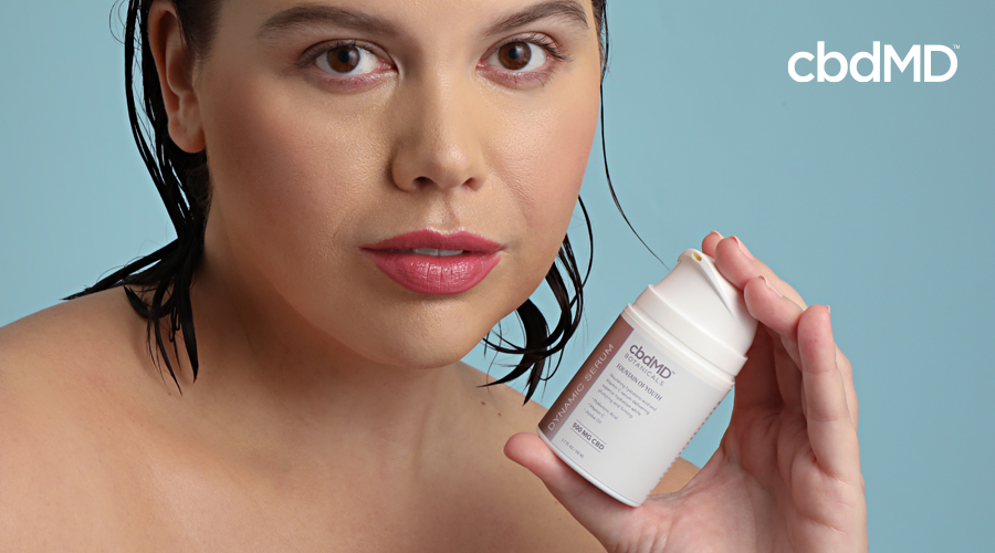 A woman holds up a bottle of fountain of youth dynamic serum from cbdmd