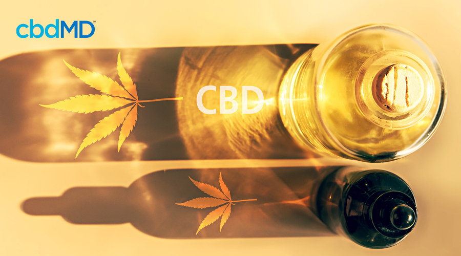 Two glass bottles of cbd oil with the sun shining through it