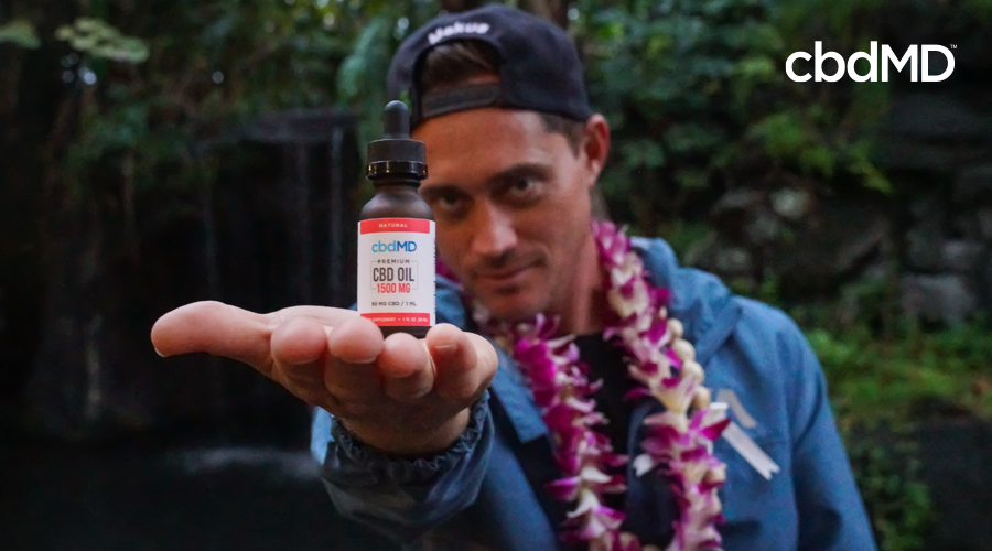 Makua Rothman holds up a bottle of cbd oil tincture in his hand towards the foreground with dark wooded areas in the background