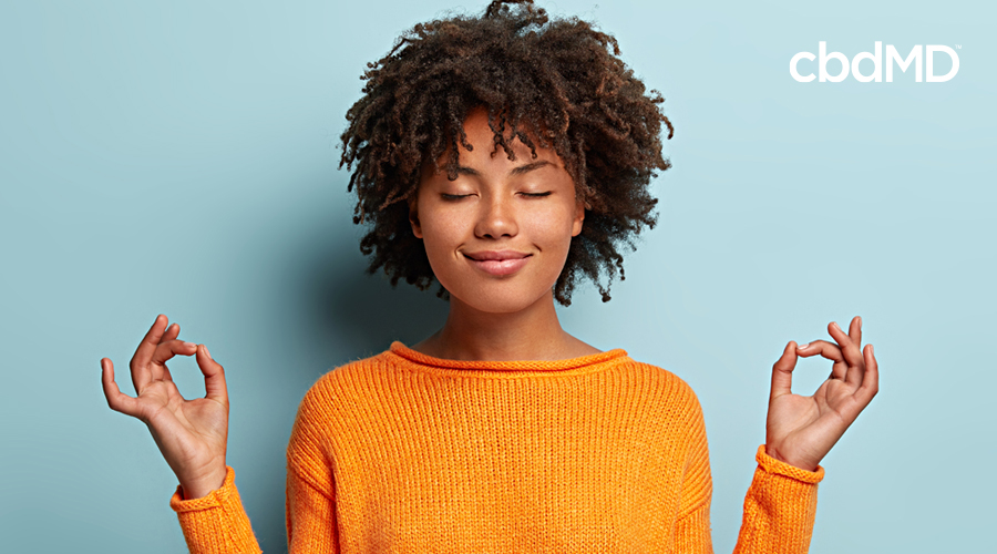 An attractive woman with naturally curly hair meditates in an orange sweater