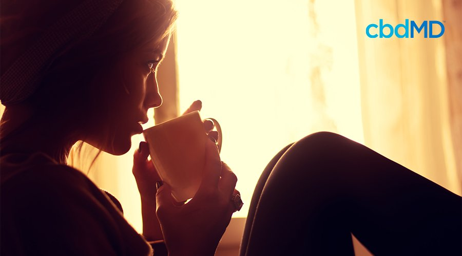 A woman sits with her knees up and sips her morning coffee from a white mug