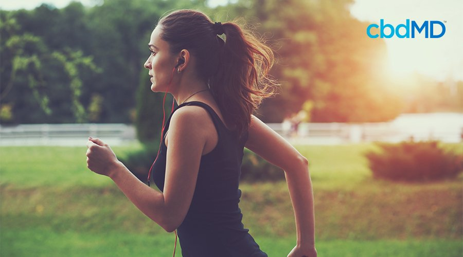 A dark haired woman goes jogging through a park with earbuds in