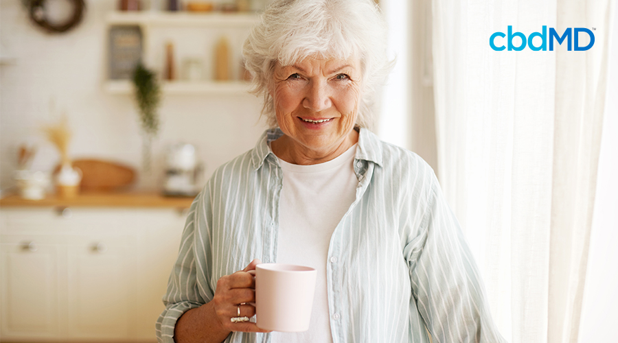 An elderly woman stands in the kitchen holding her cup of morning coffee