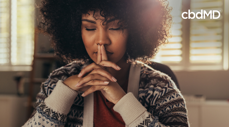 A dark skinned woman with natural hair sits with her eyes closed and her fingers steepled in front of her lips
