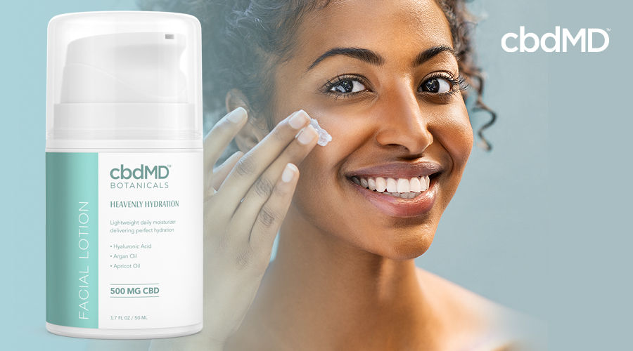 A dark skinned woman applies moisturizer with heavenly hydration in the foreground