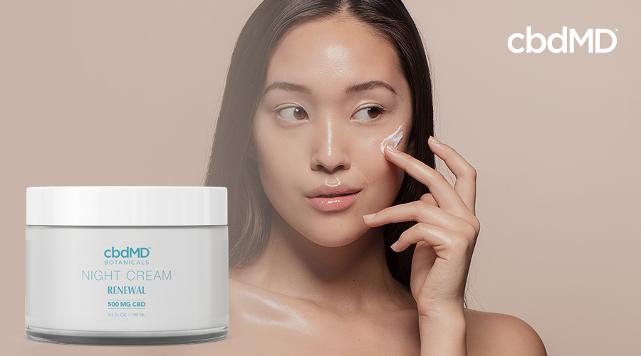 An asian woman applies night cream with a jar of night cream in the foreground