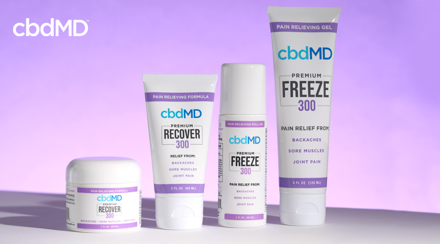 A variety of cbd topical products from cbdmd sits on a table against a purple background