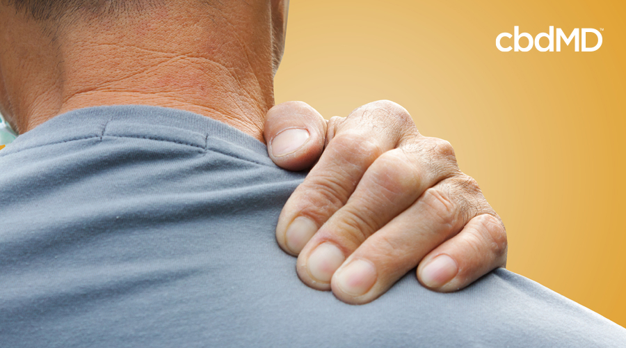 A man in a grey shirt rubes his shoulder in pain