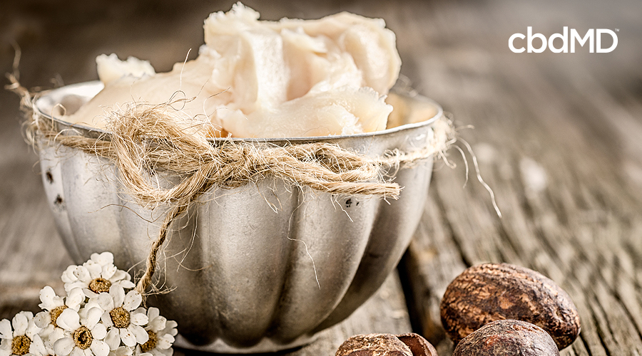 A bowl of fresh shea butter sits with a hemp cord around it on a table