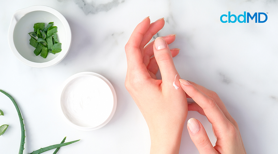 A woman rubs shea butter lotion on her hand over a marble table