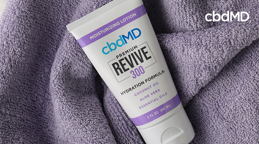 A tube of 300 mg cbd revive from cbdmd sits on a folded towel