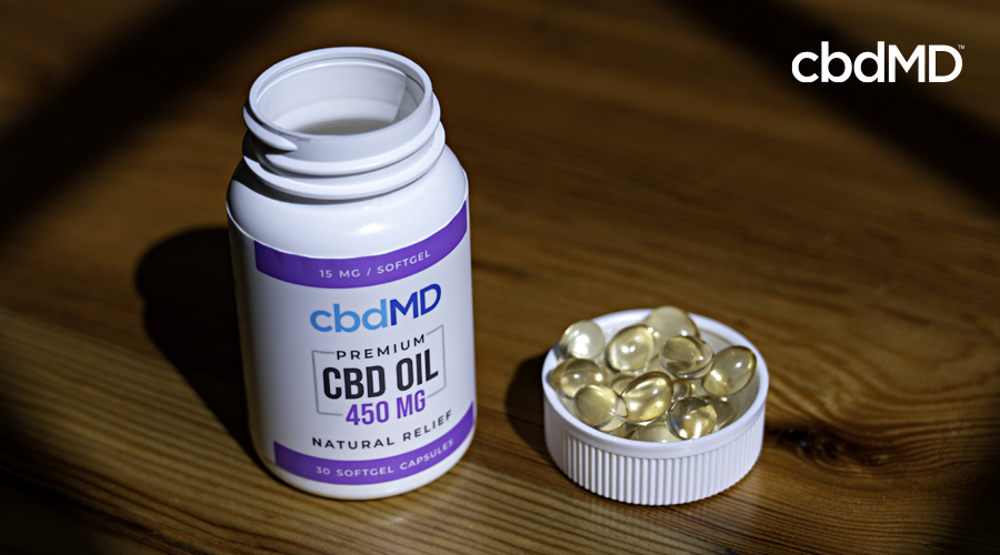 A bottle of 450 mg cbd softgel capsules from cbdmd sits on a nightstand the cap full of capsules